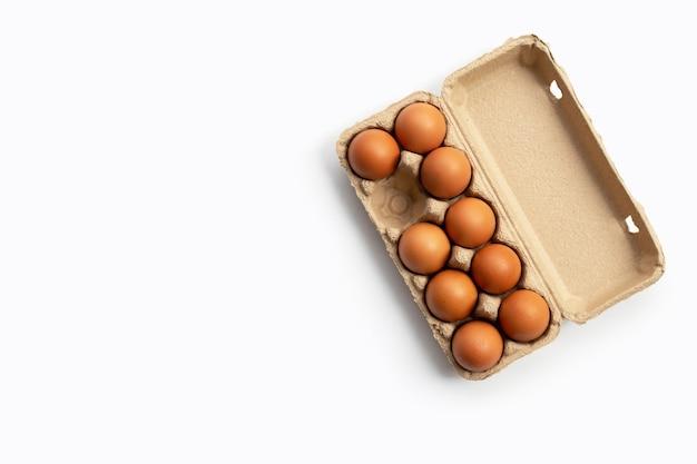 Jaja kurze w pudełku na jajka na białym tle