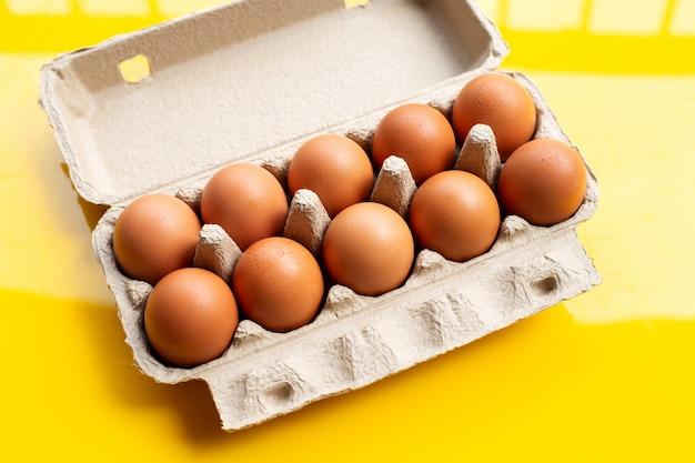 Jaja kurze w pudełku na jajka na żółtej powierzchni