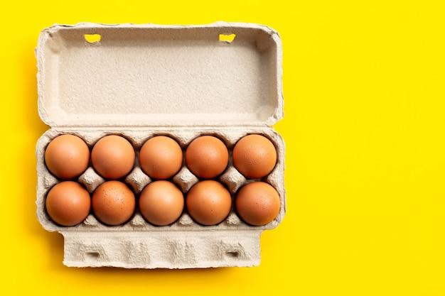 Jaja kurze w pudełku na jajka na żółtym stole.