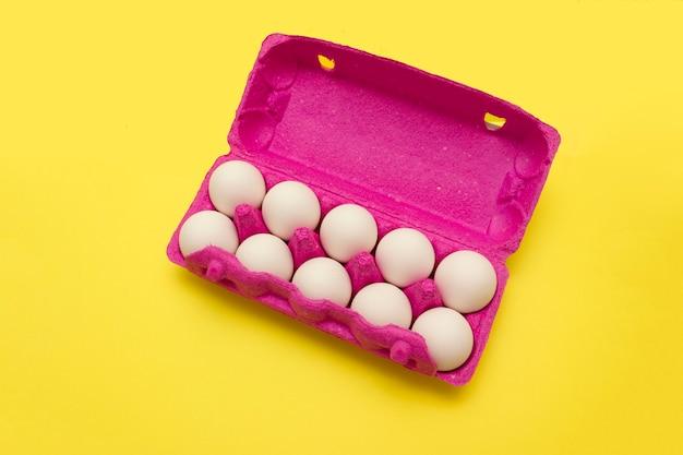 Jaja kurze w różowym pudełku na jajka na żółtym tle. kupowanie jajek przed wielkanocą.