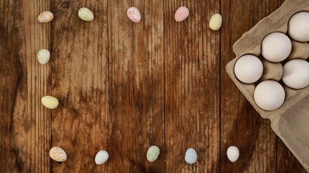 Jaja kurze w tekturowej tacy i wystrój wielkanocny na drewnianym tle., styl wiejski. ramka z miejscem na tekst