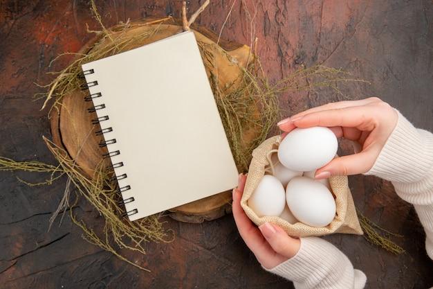 Jaja kurze z widokiem z góry w małej torebce z kobiecą ręką
