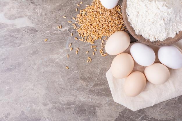 Jaja kurze z ziarnami pszenicy i szklanką mąki