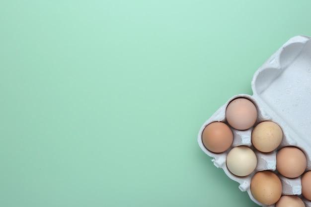 Jaja płaskie leżały. kurczaków jajka w kartonie nad zielonym tłem. widok z góry jaj.