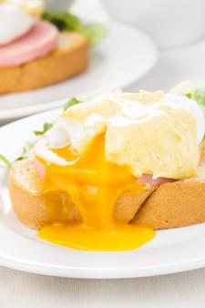 Jaja po benedyktyńsku z bliska na białym talerzu, stół do serwowania