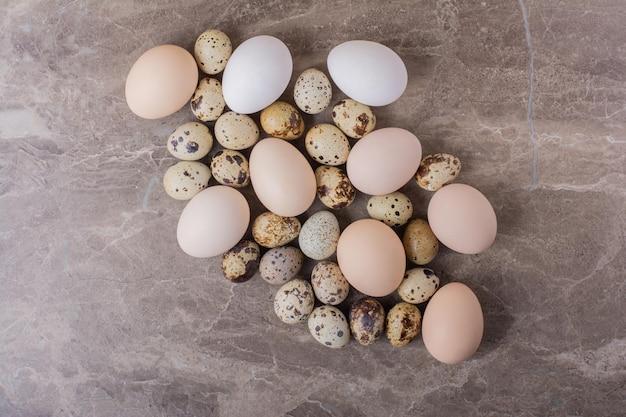 Jaja przepiórcze i kurze na białym tle na marmurowym stole.