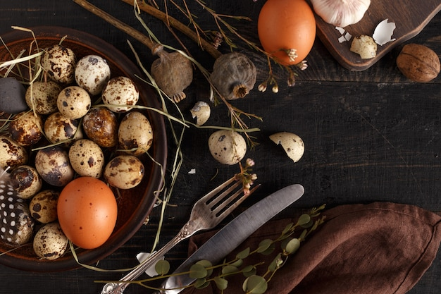 Jaja przepiórcze i kurze na glinianym talerzu na ciemnej drewnianej powierzchni.