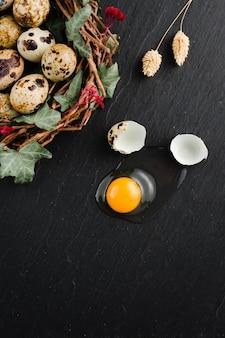 Jaja przepiórcze na czarnym tle kamienia, złamane, pęknięte jajko przepiórcze, żółtko przepiórcze. produkt ekologiczny.