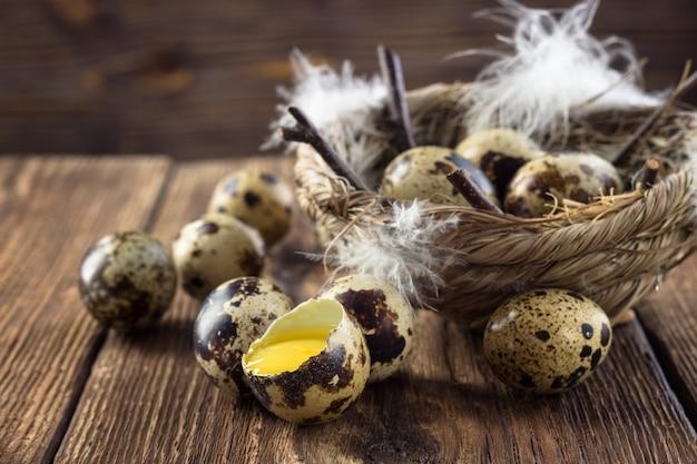 Jaja przepiórcze na drewnianym stole.