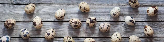Jaja przepiórcze na stare szare tło drewniane, rozmiar szeroki baner