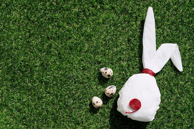 Jaja przepiórcze na zielonej trawie. biały papier do pieczenia w kształcie króliczka. koncepcja wesołych świąt. skopiuj miejsce. widok z góry