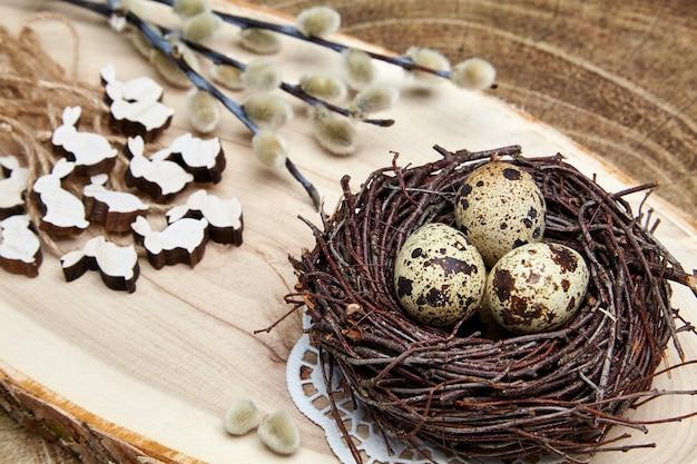 Jaja przepiórcze w gnieździe, drewniane zające i gałązki wierzby z pąkami