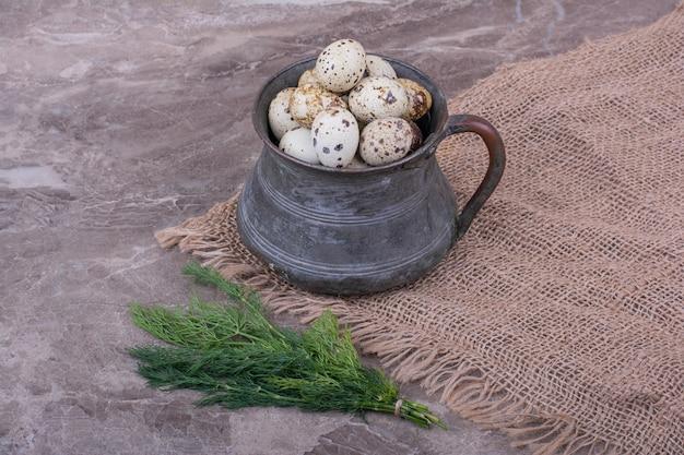 Jaja przepiórcze w metalowym garnku na płótnie