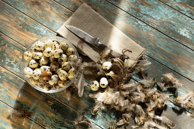 Jaja przepiórcze w misce na niebieskim tle drewnianych ozdobione piórami serwetka i nóż