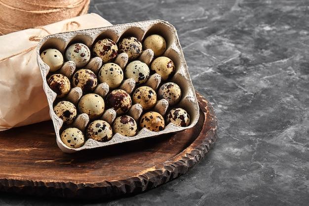 Jaja przepiórcze w szarym pudełku tekturowym. zdjęcie ze zbliżeniem. czarna powierzchnia betonu. zdrowa żywność białkowa. małe nakrapiane jajka na śniadanie.