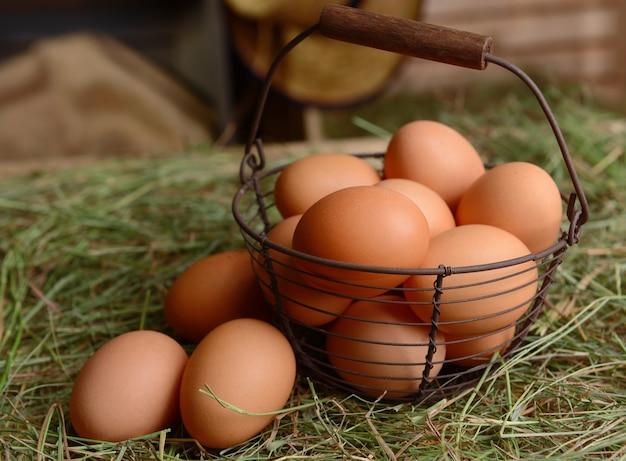 Jaja w wiklinowym koszu na stole z bliska