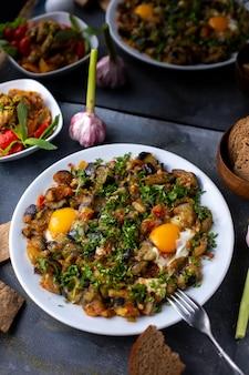 Jaja warzywa gotowane solone posypane pieprzem wraz z bochenkami chleba w białej płytce