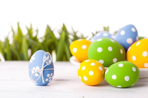 Jaja wielkanocne z kwiatkiem na świeżej zielonej trawie na białym tle