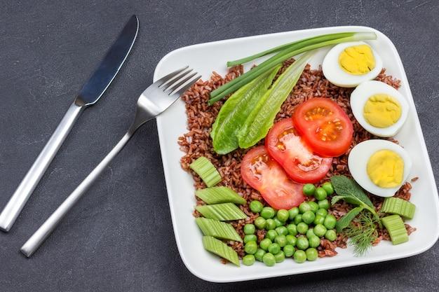 Jaja z brązowego ryżu i warzywa w białej płytce