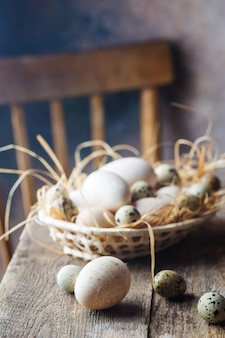 Jaja z kurczaka, przepiórki i indyka w koszu. rustykalne drewniane