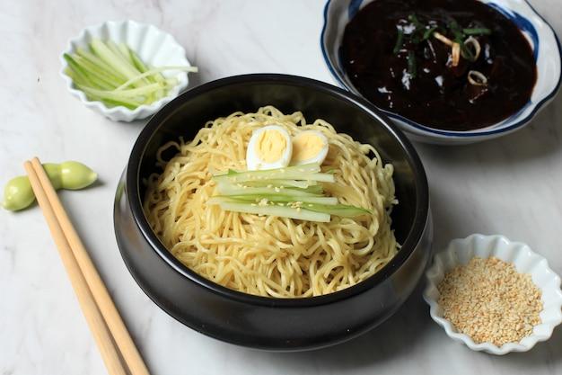 Jajangmyeon lub jjajangmyeon koreański makaron z sosem z czarnej fasoli, podawany z ogórkiem i sezamem