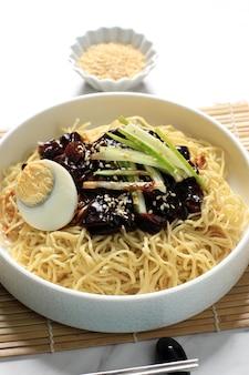 Jajangmyeon lub jjajangmyeon to koreański makaron z czarnym sosem, pionowy obraz z miejscem na kopię u góry, zbliżenie