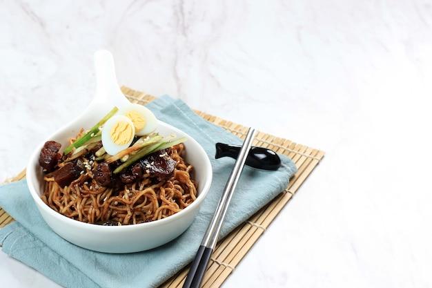 Jajangmyeon lub jjajangmyeon to koreański makaron z czarnym sosem, poziomy obraz z miejscem na kopię po prawej stronie
