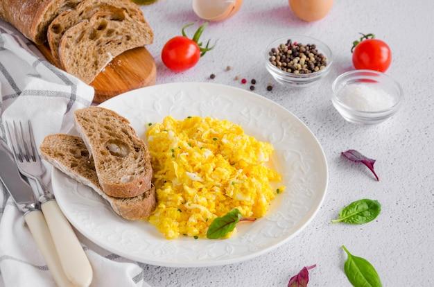 Jajecznica gotuje od organicznie świeżych jajek na białym talerzu z żytnim chlebem na lekkim tle z filiżanką kawy. zdrowe śniadanie. orientacja pozioma.