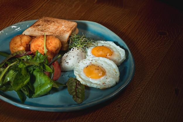 Jajecznica na mięsie ze smażonymi ziemniakami i tostami na talerzu na drewnianym stole