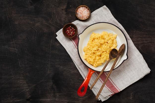 Jajecznica na śniadanie na patelni, tło ciemny drewniany stół