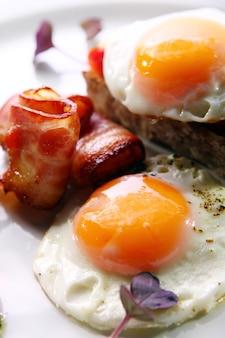 Jajecznica podawana z boczkiem i zielenią