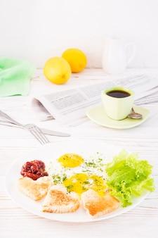 Jajecznica, smażony chleb, keczup i liście sałaty na talerzu, filiżanka kawy i gazeta na stole. śniadanie gotowe do spożycia