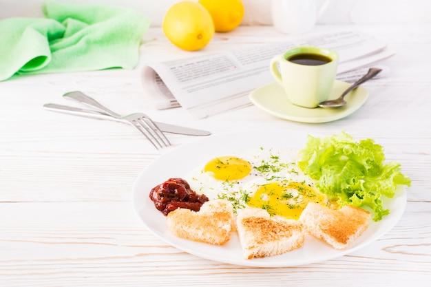 Jajecznica, smażony chleb, keczup i liście sałaty na talerzu, filiżanka kawy i gazeta na stole.