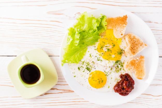 Jajecznica, smażony chleb, keczup i liście sałaty na talerzu, kawa w filiżance na stole