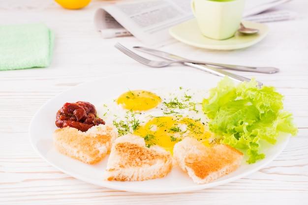 Jajecznica, smażony chleb, keczup i liście sałaty na talerzu na stole. śniadanie gotowe do spożycia