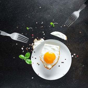 Jajecznica z białka i żółtka jajka sadzonego do jedzenia na widelcach