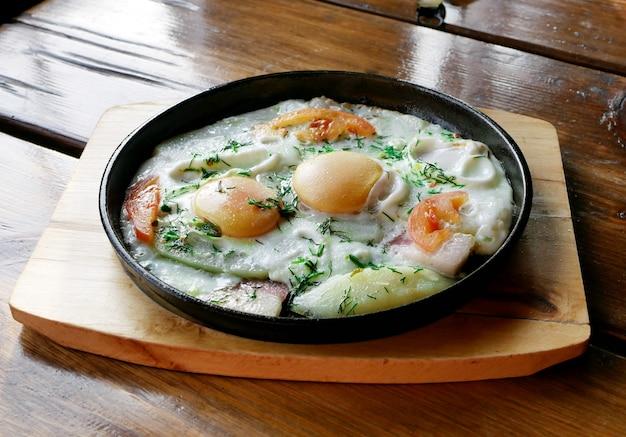 Jajecznica z boczkiem i cebulą na patelni. domowe jedzenie