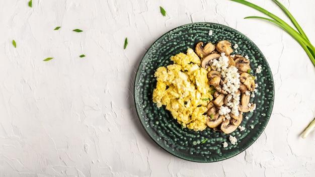 Jajecznica z pieczarkami i twarogiem. pyszne śniadanie lub przekąska na lekkim stole, widok z góry.