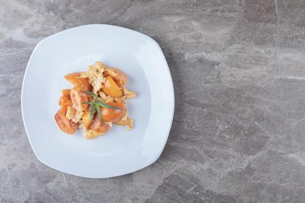 Jajecznica z pomidorami na białym talerzu.