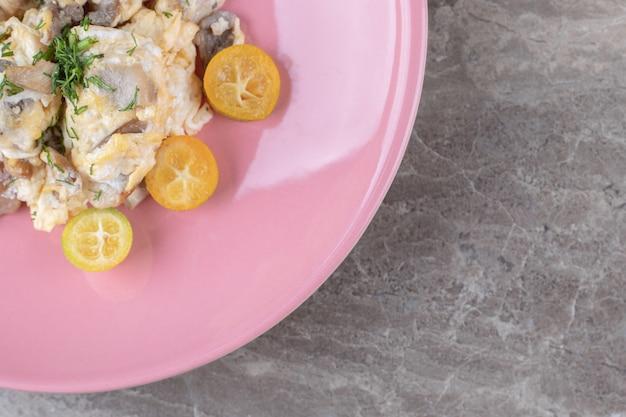 Jajecznica z warzywami na różowym talerzu.