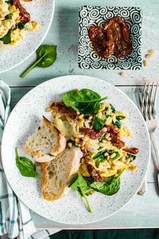 Jajecznica ze szpinakiem i suszonymi pomidorami fotografia żywności