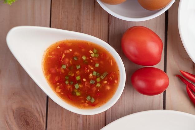 Jajka, chili, pomidor i sos w białym talerzu na drewnianym.