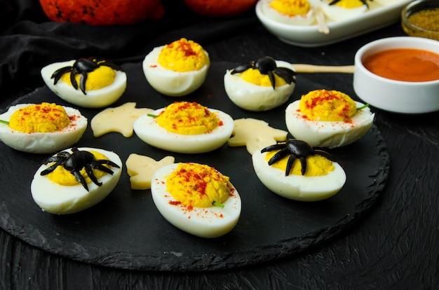 Jajka faszerowane halloween z serem i musztardą na czarnym kamieniu.