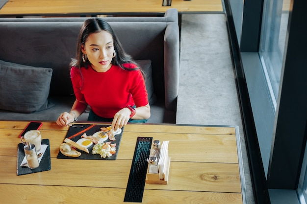 Jajka i kawa. ciemnowłosa stylowa kobieta je jajka i pije kawę na śniadanie