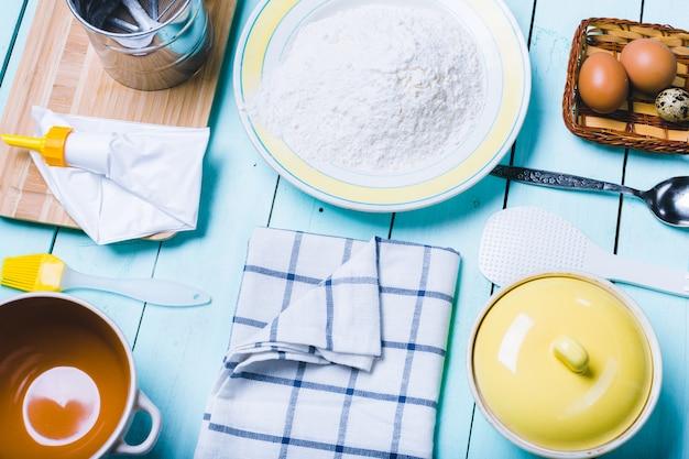Jajka i mąka z wałkiem do ciasta. na drewnianym tle.