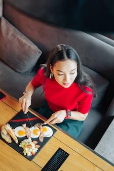 Jajka i sałatka. widok z góry stylowej szczupłej ciemnowłosej kobiety jedzącej smaczne jajka i sałatkę