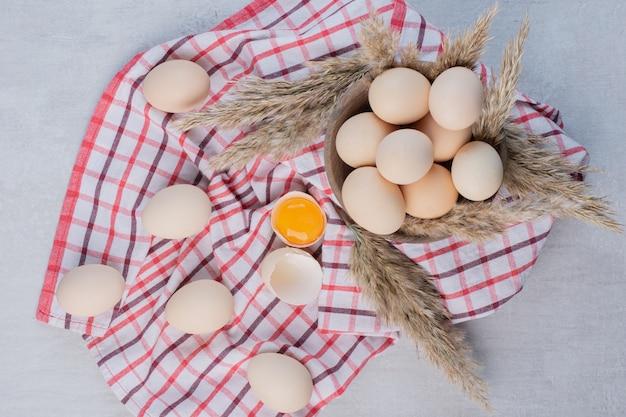 Jajka i źdźbła trawy z piór w misce i obok niej na ręczniku na marmurowym stole.