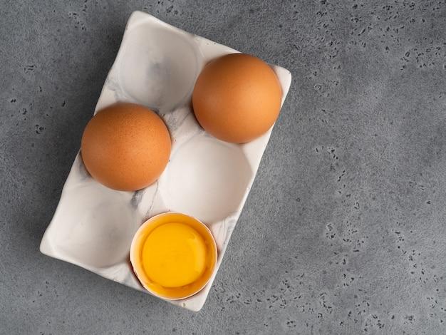 Jajka i żółtka, skorupka w białym ceramicznym uchwycie na szarym tle betonu. widok z góry.