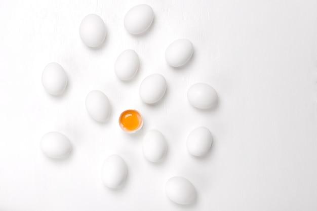 Jajka. jeden pęknięty i grupa całych niespotykanych jajek na białym tle.