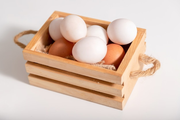 Jajka kaczki i kurze jaja są wkładane do drewnianego kosza